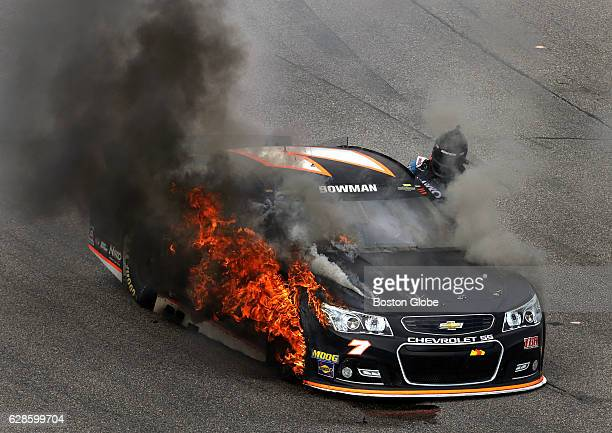 Alex Bowman exits his car after it burst into flames after a pit stop during the NASCAR Sprint Cup New Hampshire 301 at New Hampshire Motor Speedway...