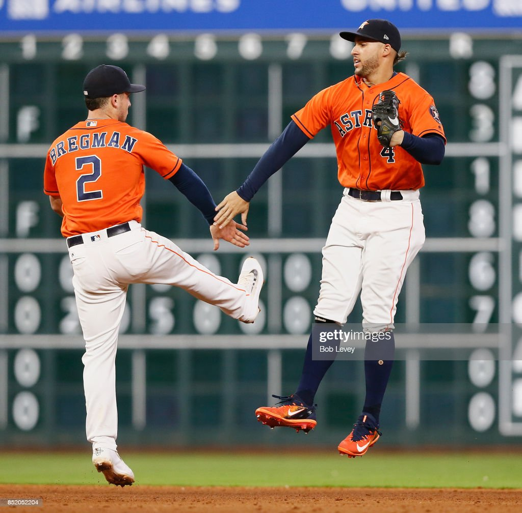 Alex Bregman #2 of the Houston Astros and George Springer #4 celebrate a 3-0 win over the Los Angeles Angels of Anaheim at Minute Maid Park on September 22, 2017 in Houston, Texas.