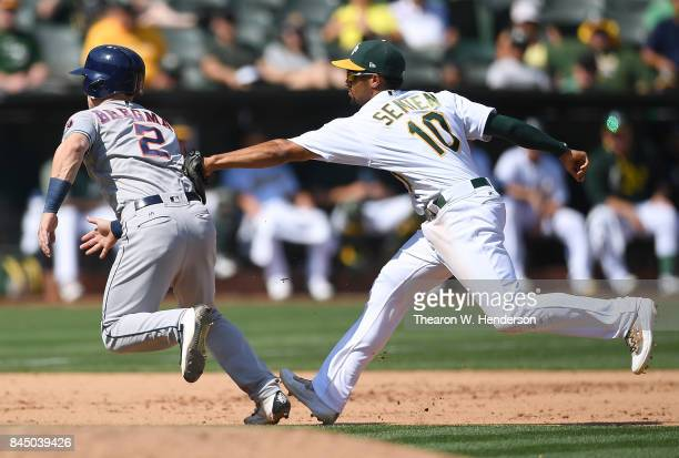 Alex Bregman of the Houston Astros caught in a rundown gets tagged out by Marcus Semien of the Oakland Athletics in the top of the fifth inning...