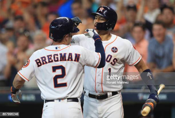 Alex Bregman of the Houston Astros celebrates with Carlos Correa after hitting a home run in the first inning against the Boston Red Sox during game...