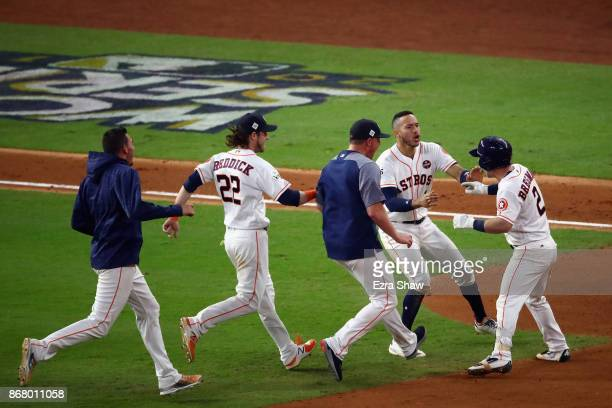 Alex Bregman of the Houston Astros celebrates with teammates after hitting a gamewinning single during the tenth inning against the Los Angeles...