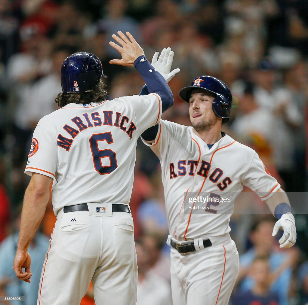 Alex Bregman #2 of the Houston Astros gets a high five from Jake Marisnick #6 after hitting a three-run home run in the eighth inning at Minute Maid Park on August 23, 2017 in Houston, Texas.