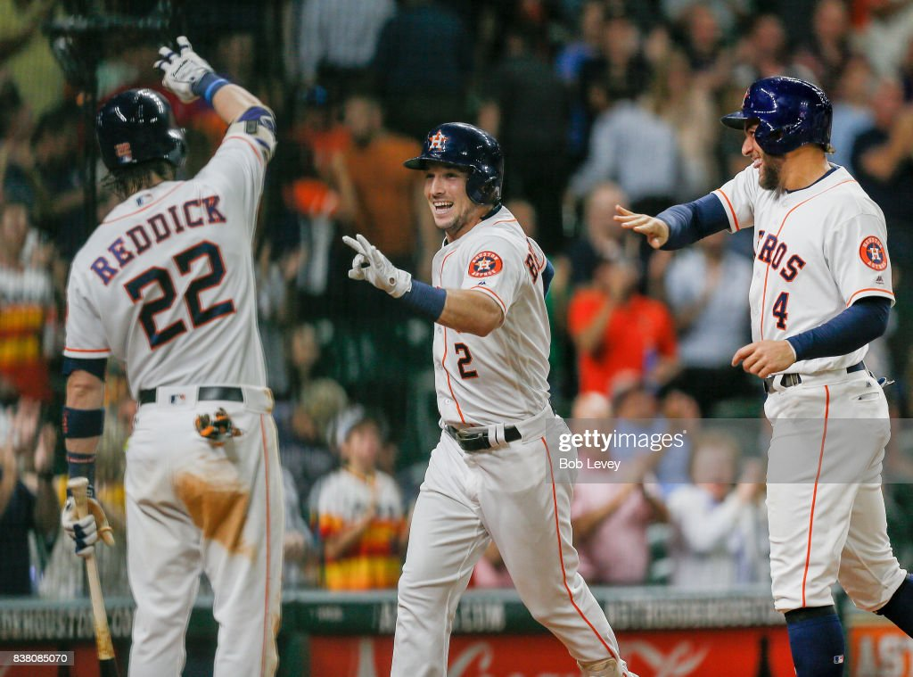 Alex Bregman #2 of the Houston Astros is congratulated by George Springer #4 and Josh Reddick #22 after a three-run home run in the eighth inning against the Washington Nationals at Minute Maid Park on August 23, 2017 in Houston, Texas.