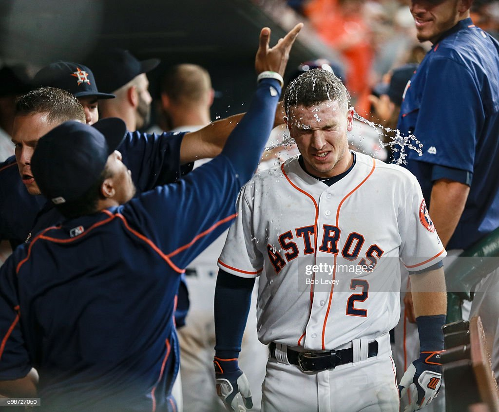 Alex Bregman of the Houston Astros is doused with water and sunflower seeds after hitting a home run in the third inning against the Tampa Bay Rays...