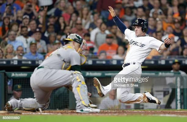 Alex Bregman of the Houston Astros slides home against Bruce Maxwell of the Oakland Athletics in the fifth inning at Minute Maid Park on August 19...
