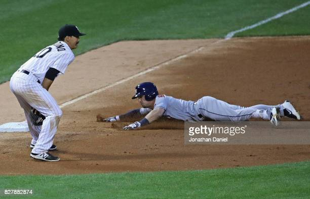 Alex Bregman of the Houston Astros slides into third base with a three run triple in the 2nd inning as Tyler Saladino of the Chicago White Sox takes...