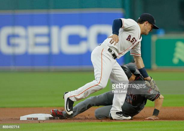 Alex Bregman of the Houston Astros tags out AJ Pollock of the Arizona Diamondbacks as he tries steal second base in the first inning at Minute Maid...
