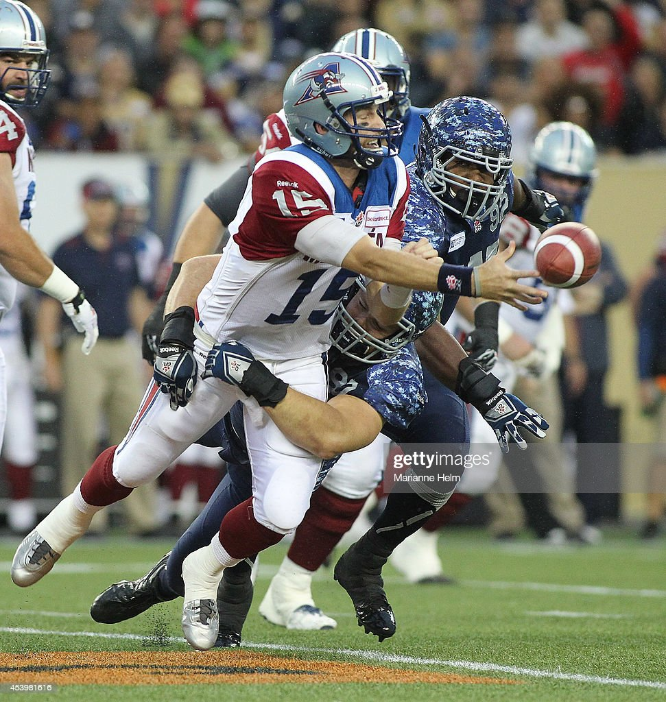 Alex Brink #15 of the Montreal Alouettes gets rid of the ball just in time as he is tackled by Greg Peach #90 of the Winnipeg Blue Bombers in first quarter action in a CFL game at Investors Group Field on August 22, 2014 in Winnipeg, Manitoba, Canada.