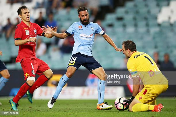 Alex Brosque of Sydney FC is challenged by Isaias of United and goalkeeper Eugene Galekovic of United during the round 16 ALeague match between...