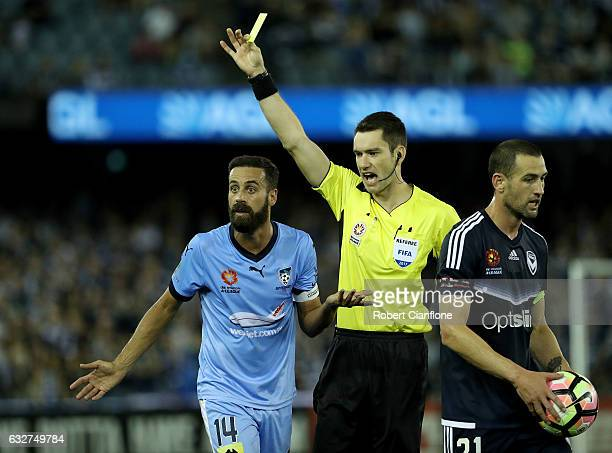 Alex Brosque of Sydney FC is shown the yellow card by referee Jarred Gillett during the round 17 ALeague match between the Melbourne Victory and...