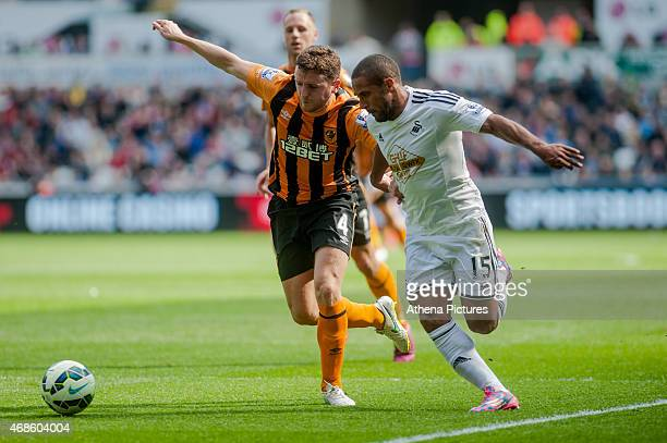 Alex Bruce of Hull City and Wayne Routledge of Swansea City in action during the Premier League match between Swansea City and Hull City at Liberty...