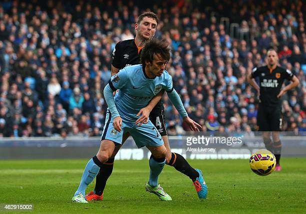 Alex Bruce of Hull City tangles in the penalty area with David Silva of Manchester City during the Barclays Premier League match between Manchester...