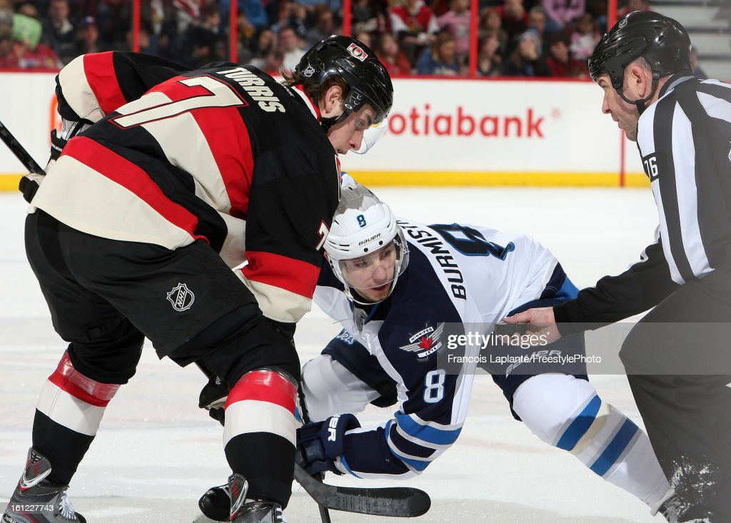 Alex Burmistrov #8 of the Winnipeg Jets looks at the puck during a faceoff against <a gi-track='captionPersonalityLinkClicked' href=/galleries/search?phrase=Kyle+Turris&family=editorial&specificpeople=4251834 ng-click='$event.stopPropagation()'>Kyle Turris</a> #7 of the Ottawa Senators during an NHL game at Scotiabank Place on February 9, 2013 in Ottawa, Ontario, Canada.