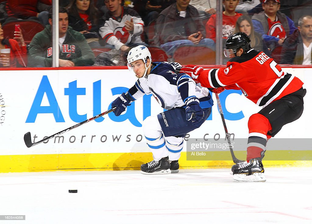 Alex Burmistrov #8 of the Winnipeg Jets skates against <a gi-track='captionPersonalityLinkClicked' href=/galleries/search?phrase=Andy+Greene&family=editorial&specificpeople=3568726 ng-click='$event.stopPropagation()'>Andy Greene</a> #6 of the New Jersey Devils during their game at the Prudential Center on February 24, 2013 in Newark, New Jersey.