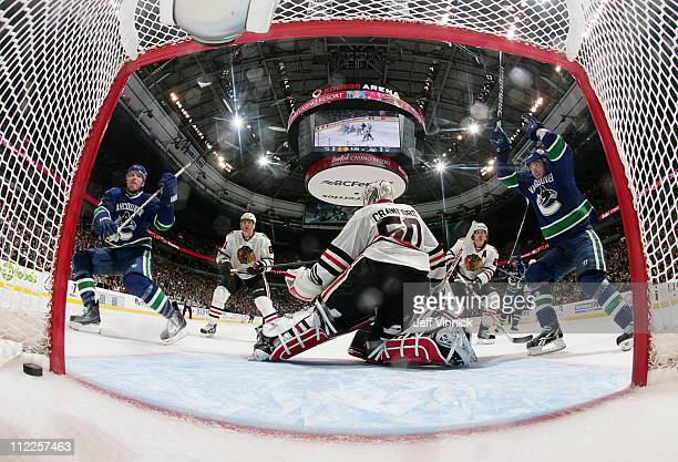 Alex Burrows and Christian Ehrhoff of the Vancouver Canucks celebrate the game winning goal of teammate Daniel Sedin on Corey Crawford of the Chicago...