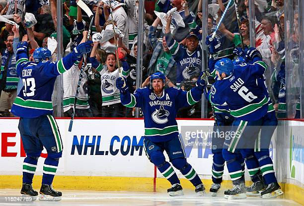 Alex Burrows celebrates with teammates Manny Malhotra Sami Salo Daniel Sedin and Alexander Edler of the Vancouver Canucks after he scores the game...