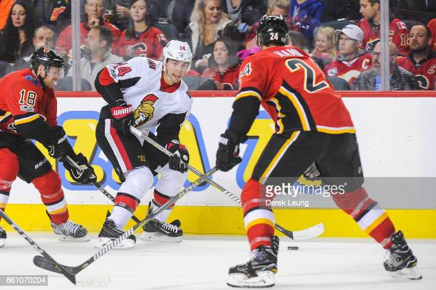 Alex Burrows of the Ottawa Senators skates with the puck against Travis Hamonic of the Calgary Flames during an NHL game at Scotiabank Saddledome on...