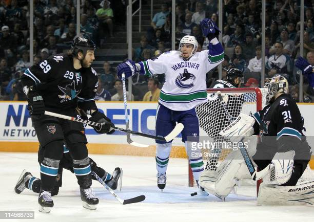 Alex Burrows of the Vancouver Canucks celebrates after scoring from the left wing on a pass through the crease past goaltender Antti Niemi of the San...