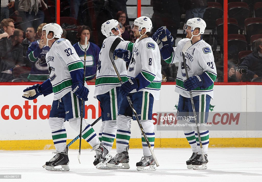 Alex Burrows #14 of the Vancouver Canucks celebrates their win with team mates <a gi-track='captionPersonalityLinkClicked' href=/galleries/search?phrase=Dale+Weise&family=editorial&specificpeople=5527418 ng-click='$event.stopPropagation()'>Dale Weise</a> #32, Chris Tanev #8 and <a gi-track='captionPersonalityLinkClicked' href=/galleries/search?phrase=Daniel+Sedin&family=editorial&specificpeople=202492 ng-click='$event.stopPropagation()'>Daniel Sedin</a> #22 following an NHL game against the Ottawa Senators at Canadian Tire Centre on November 28, 2013 in Ottawa, Ontario, Canada.