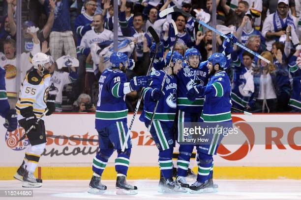 Alex Burrows of the Vancouver Canucks celebrates with his teammates after scoring a goal against Tim Thomas of the Boston Bruins in the middle of the...