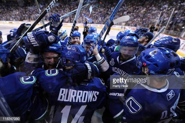 Alex Burrows of the Vancouver Canucks celebrates with his teammates after scoring a goal in overtime against Zdeno Chara of the Boston Bruins to win...