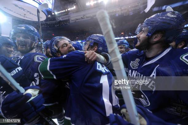 Alex Burrows of the Vancouver Canucks celebrates with his teammates after scoring a goal in overtime against Zdeno Chara and Tim Thomas of the Boston...