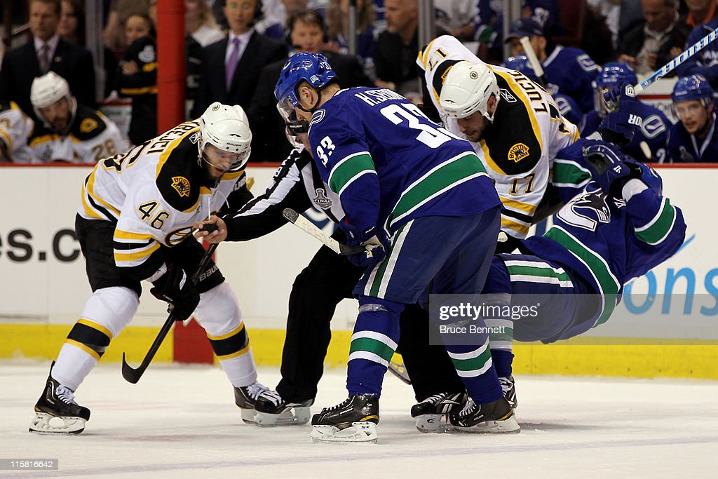 Alex Burrows of the Vancouver Canucks gets knocked down by Milan Lucic of the Boston Bruins prior to a face off between David Krejci and Henrik Sedin...