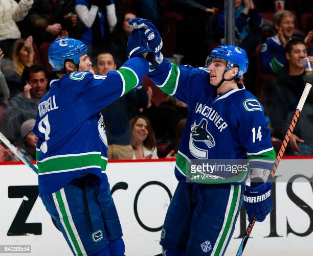 Alex Burrows of the Vancouver Canucks is congratulated by teammate Willie Mitchell after scoring during their game against the St Louis Blues at...