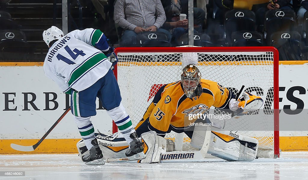 Alex Burrows #14 of the Vancouver Canucks scores a short-handed goal against Pekka Rinne #35 of the Nashville Predators during an NHL game at Bridgestone Arena on March 31, 2015 in Nashville, Tennessee.