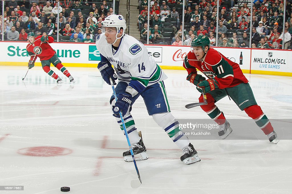 Alex Burrows #14 of the Vancouver Canucks skates with the puck while <a gi-track='captionPersonalityLinkClicked' href=/galleries/search?phrase=Zach+Parise&family=editorial&specificpeople=213606 ng-click='$event.stopPropagation()'>Zach Parise</a> #11 of the Minnesota Wild defends during the game on February 7, 2013 at the Xcel Energy Center in Saint Paul, Minnesota.