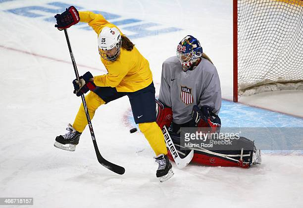 Alex Carpenter of United States takes a shot past teammate goaltender Brianne McLaughlin during a training session ahead of the Sochi 2014 Winter...