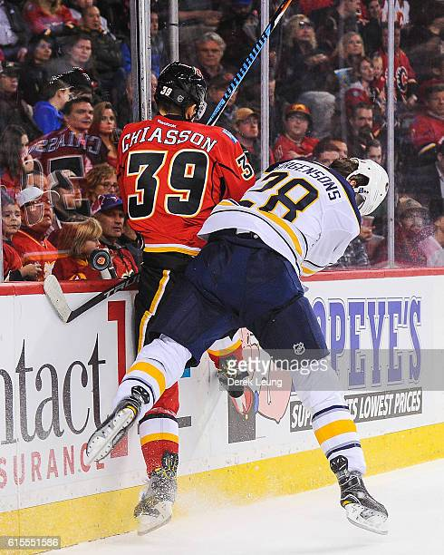 Alex Chiasson of the Calgary Flames gets checked by Zemgus Girgensons of the Buffalo Sabres during an NHL game at Scotiabank Saddledome on October 18...