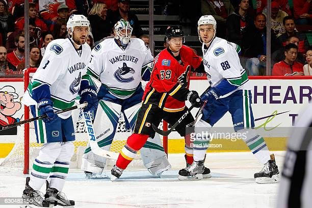 Alex Chiasson of the Calgary Flames skates in front of the net against Nikita Tryamkin and Jacob Markstrom of the Vancouver Canucks during an NHL...