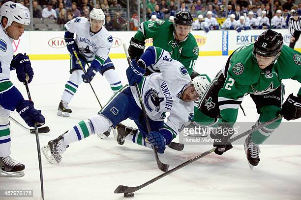 Alex Chiasson of the Dallas Stars skates the puck away from Brad Richardson of the Vancouver Canucks in the first period at American Airlines Center...