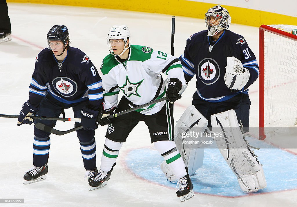 Alex Chiasson #12 of the Dallas Stars stands between Jacob Trouba #8 and goaltender Ondrej Pavelec #31 of the Winnipeg Jets as they keep an eye on the play during second period action at the MTS Centre on October 11, 2013 in Winnipeg, Manitoba, Canada.