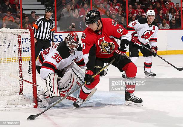 Alex Chiasson of the Ottawa Senators controls the puck outside the crease for a scoring chance against Cory Schneider and Andy Greene of the New...