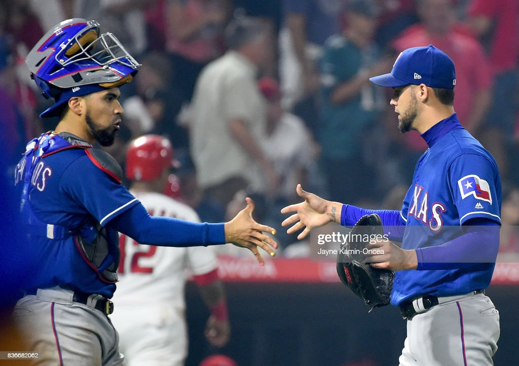 Alex Claudio #58 shakes hands with Robinson Chirinos #61 of the Texas Rangers after the final out of the ninth inning of the game against the Los Angeles Angels of Anaheim at Angel Stadium of Anaheim on August 21, 2017 in Anaheim, California.