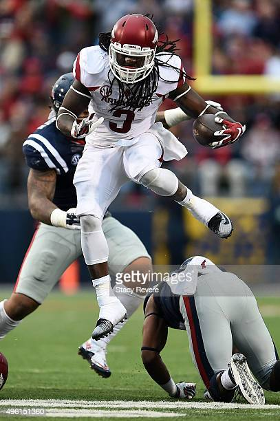 Alex Collins of the Arkansas Razorbacks leaps over DeMarquis Gates of the Mississippi Rebels during the second quarter of a game at VaughtHemingway...