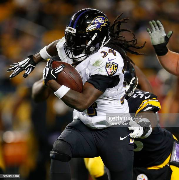 Alex Collins of the Baltimore Ravens carries the ball against Arthur Moats of the Pittsburgh Steelers in the third quarter during the game at Heinz...