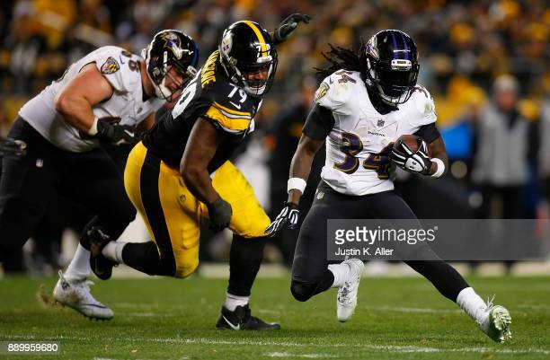 Alex Collins of the Baltimore Ravens carries the ball against Javon Hargrave of the Pittsburgh Steelers in the third quarter during the game at Heinz...
