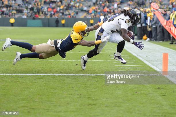 Alex Collins of the Baltimore Ravens rushes for a touchdown after avoiding a tackle by Ha Ha ClintonDix of the Green Bay Packers during the second...