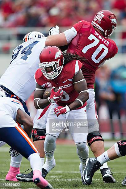 Alex Collins runs behind the block of Dan Skipper of the Arkansas Razorbacks during a game against the UT Martin Skyhawks at Razorback Stadium on...