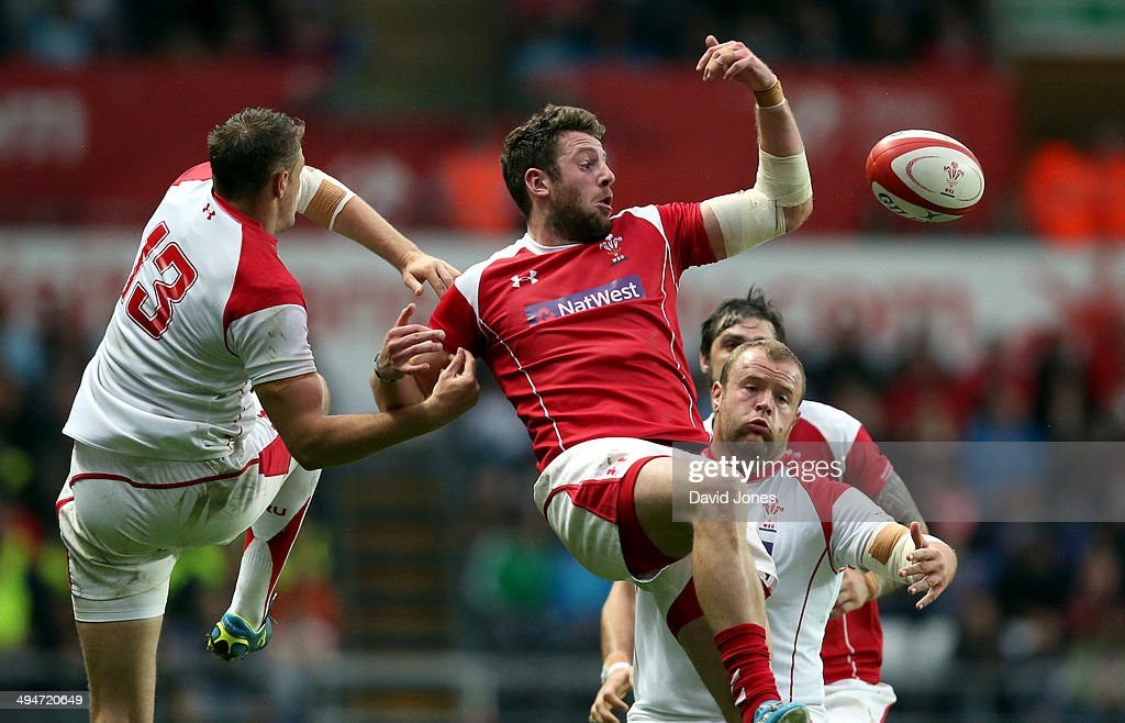 Alex Cuthbert of the Probables spills a high ball under pressure from Cory Allen of the Possibles during the Wales Senior Trial between Probables v...