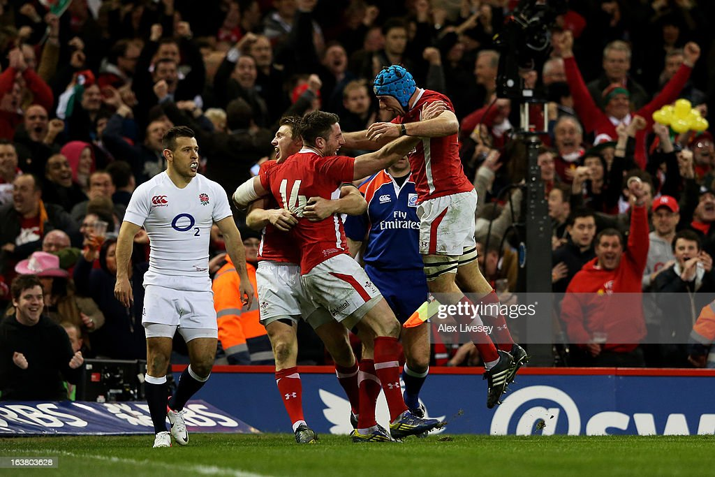 Alex Cuthbert of Wales celebrates with teammates Dan Biggar and Justin Tipuric after scoring his team's second try during the RBS Six Nations match...