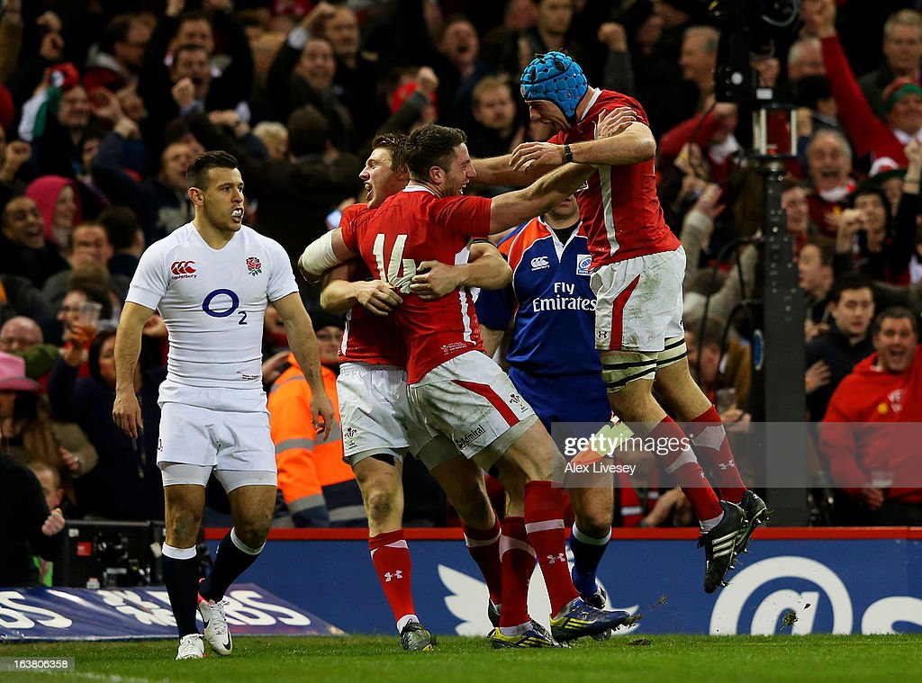 <a gi-track='captionPersonalityLinkClicked' href=/galleries/search?phrase=Alex+Cuthbert&family=editorial&specificpeople=6143846 ng-click='$event.stopPropagation()'>Alex Cuthbert</a> #14 of Wales celebrates with teammates <a gi-track='captionPersonalityLinkClicked' href=/galleries/search?phrase=Dan+Biggar&family=editorial&specificpeople=5607224 ng-click='$event.stopPropagation()'>Dan Biggar</a> (L) and Justin Tipuric (R) after scoring his team's second try during the RBS Six Nations match between Wales and England at Millennium Stadium on March 16, 2013 in Cardiff, Wales.