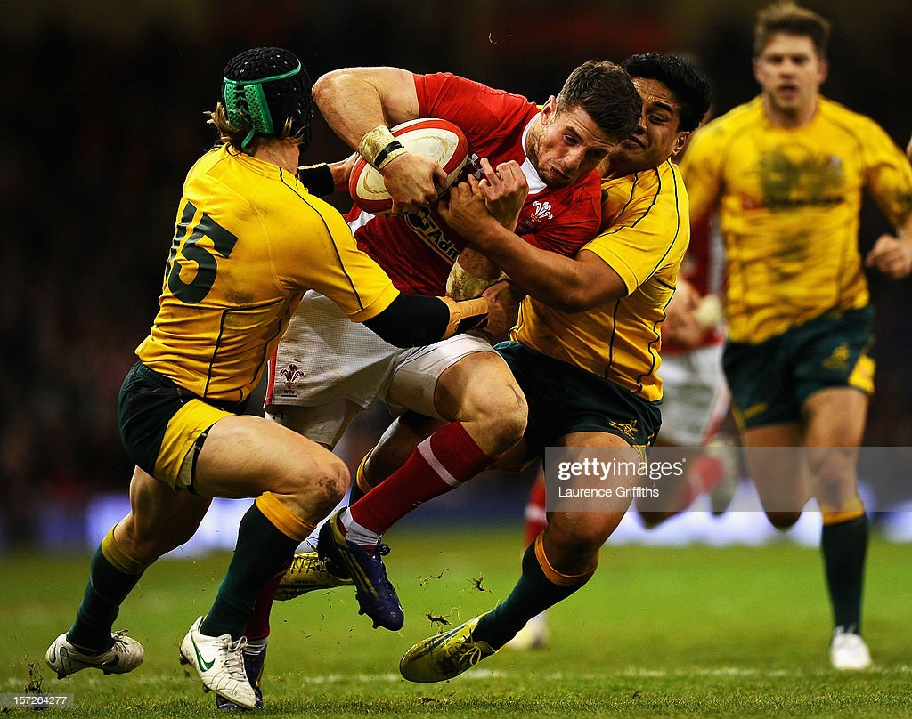 Alex Cuthbert of Wales is tackled by Berrick Barnes and Ben Tapuai of Australia during the International match between Wales and Australia at...