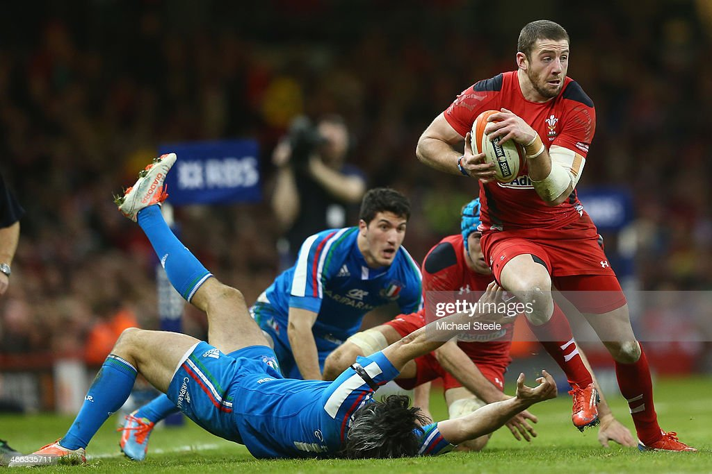 Alex Cuthbert of Wales powers his way past Luke McLean of Italy during the RBS Six Nations match between Wales and Italy at the Millenium Stadium on...