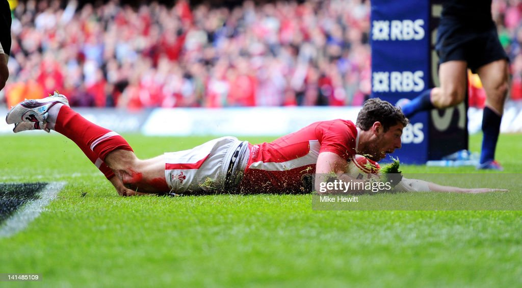 Alex Cuthbert of Wales slides over to score the opening try during the RBS Six Nations Championship match between Wales and France at the Millennium...
