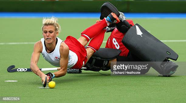 Alex Danson of England shoots past Sally Rutherford of New Zealand in the penalty shuttles during the Women's Hockey Semi Final between New Zealand...