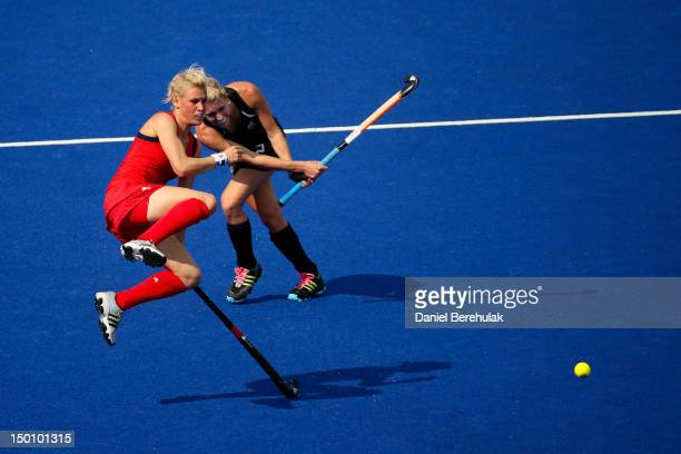 Alex Danson of Great Britain jumps out of the way of Emily Naylor of New Zealand during the first half of the Women's Hockey bronze medal match on...
